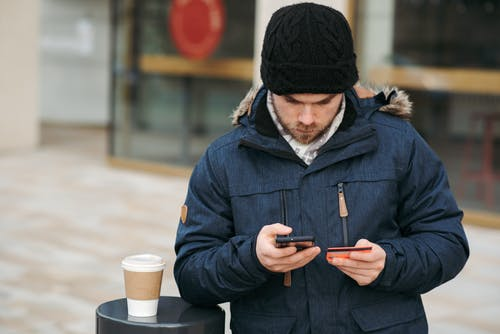 Focused male holding credit card while making payment with smartphone on street
