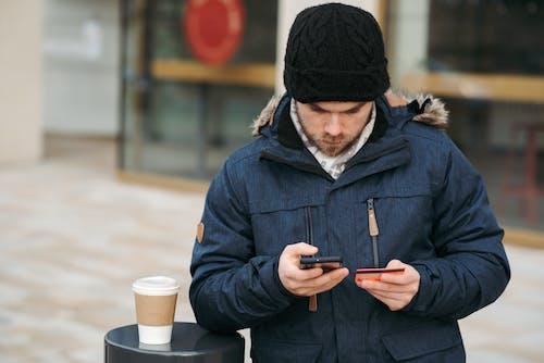 Uomo In Berretto In Maglia Nera E Giacca Nera Che Tiene Smartphone
