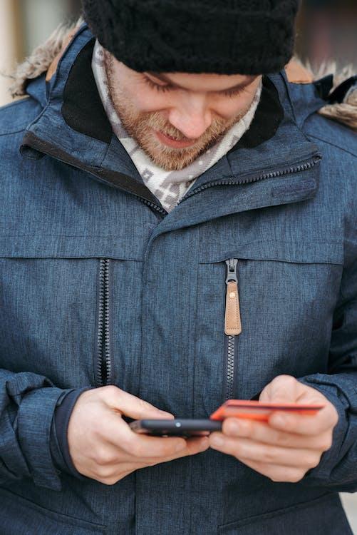 Uomo In Giacca Con Zip Blu Che Tiene Smartphone Nero