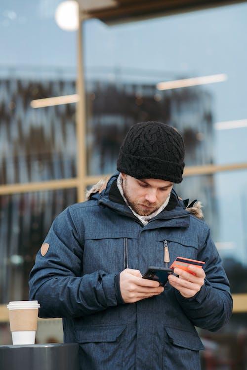 Uomo In Berretto Nero E Giacca Nera Che Tiene Smartphone Nero