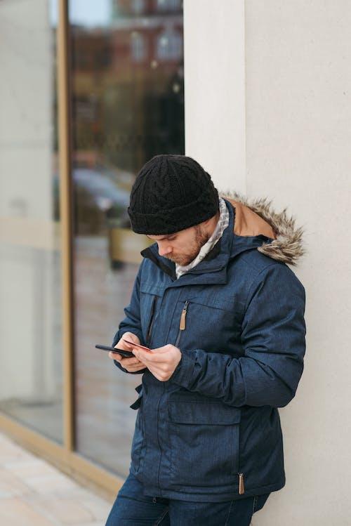 Uomo In Giacca Nera Utilizza Lo Smartphone