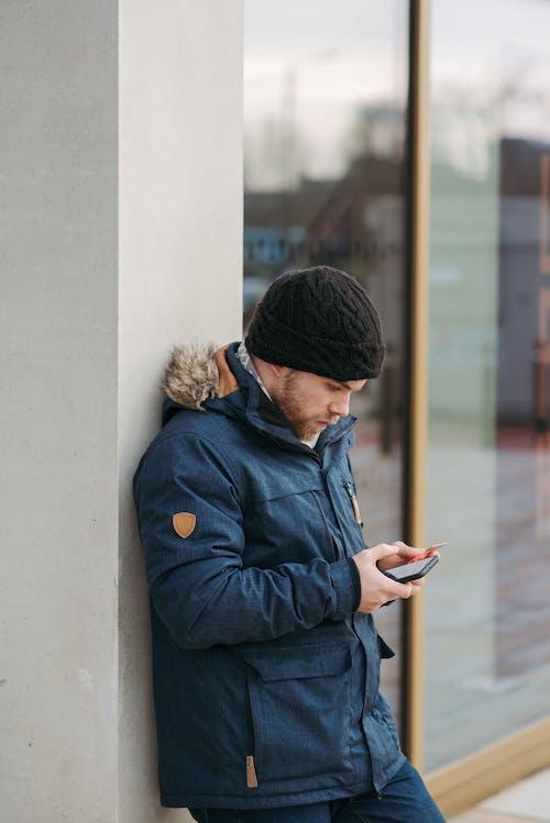 Mavi Ceketli Ve Siyah örgü şapkalı Adam Akıllı Telefon Kullanarak