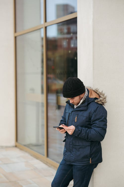 Thoughtful man browsing smartphone on street in daylight