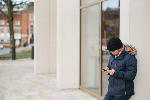 Uomo In Giacca Nera E Berretto In Maglia Nera In Piedi Vicino A Edificio In Cemento Bianco