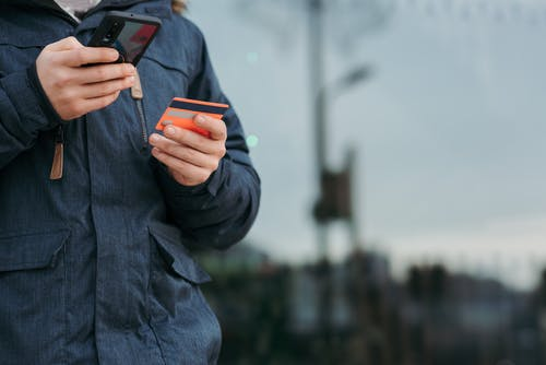 Male taking photo of credit card on smartphone on street in daytime