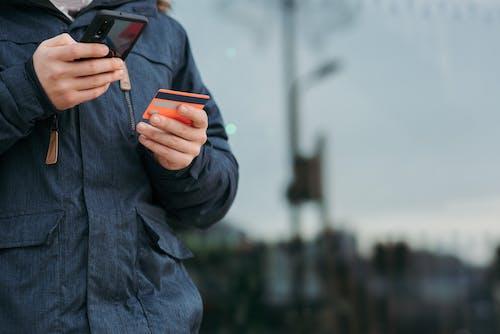 Orang Dengan Jaket Hitam Memegang Smartphone Hitam
