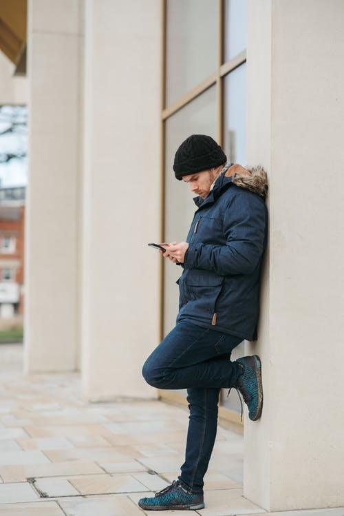 Side view of thoughtful man in warm outwear standing with raised leg near building and browsing mobile phone in daytime