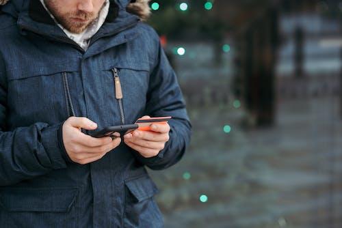 Homem De Jaqueta Preta Segurando Um Smartphone