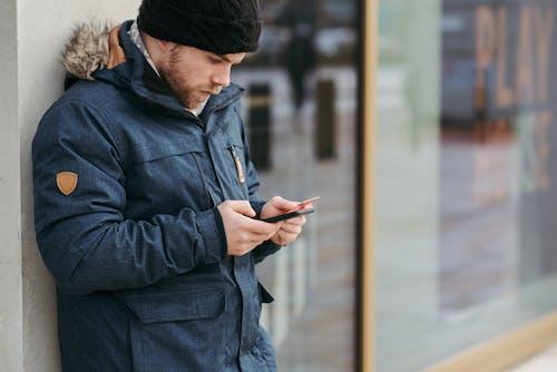 Mann In Schwarzer Strickmütze Und Schwarzer Jacke Mit Smartphone