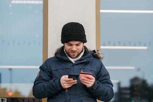Pria Dengan Topi Rajut Hitam Dan Jaket Hitam Memegang Smartphone Hitam