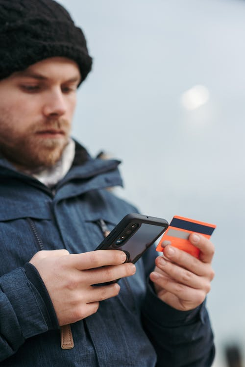 Crop man in warm clothes entering details of credit card on mobile phone while making online purchases on street in daytime