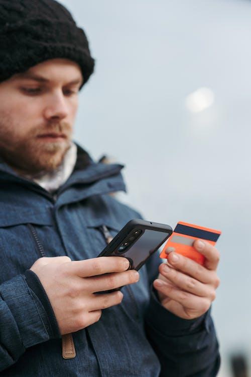 Pria Berbaju Denim Biru Memegang Smartphone Hitam