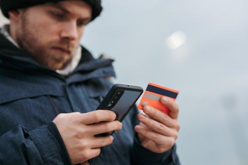 Pria Berjaket Hitam Memegang Smartphone Hitam