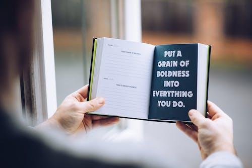 Orang Yang Memegang Buku Putih Dan Biru