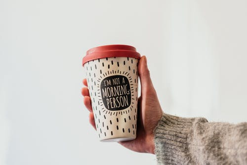 Crop unrecognizable person demonstrating message on paper cup of takeaway hot drink with ornament on white background