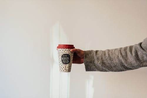Crop anonymous person in soft wear demonstrating paper cup of takeaway hot drink with ornament and inscription