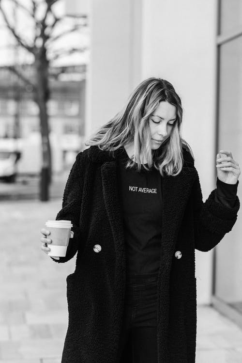 Black and white of adult female in coat with takeaway hot beverage looking down on urban pavement
