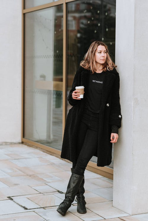 Melancholic woman with takeaway coffee on city street
