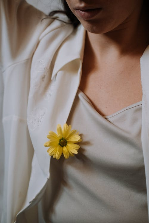 Crop unrecognizable tender female with blossoming yellow flower with pleasant scent and delicate petals on wear