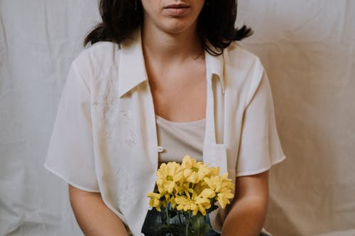 Crop unemotional brunette in white clothes with yellow gentle chrysanthemum flowers sitting against white background in light room