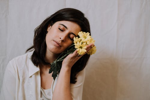 Positive female in white wear touching face with yellow fragrant chrysanthemum flowers while sitting with eyes closed in light room
