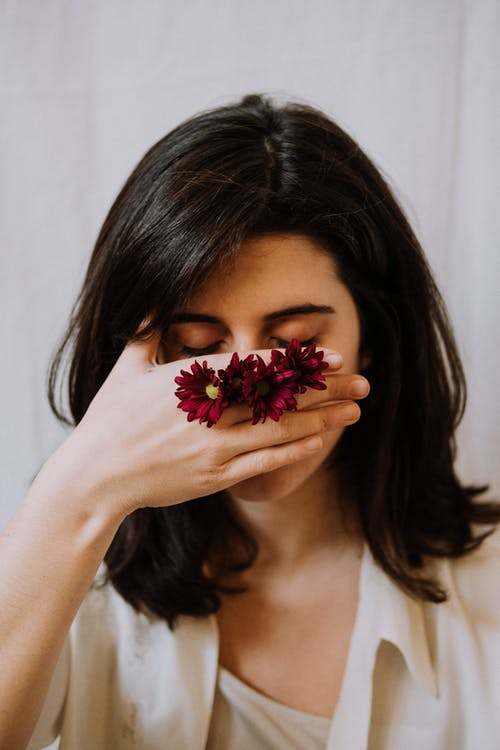 Peaceful woman with closed eyes covering face with hand decorated with blossoming flowers