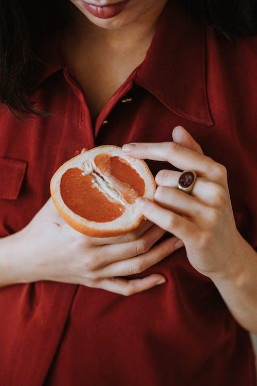 Woman with half of ripe grapefruit