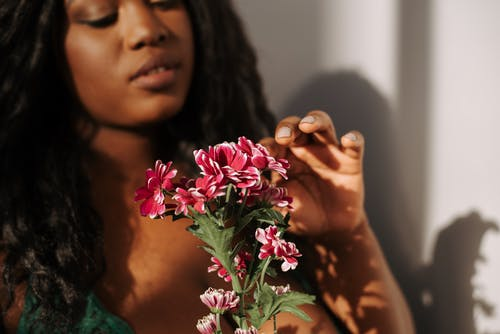 Crop attractive African American female with long wavy hair touching gentle pink pelargonium flower in bedroom