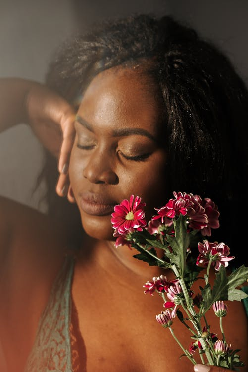 Beautiful sensitive African American female touching face with hand and fragrant pink geranium flowers while standing with eyes closed in bedroom