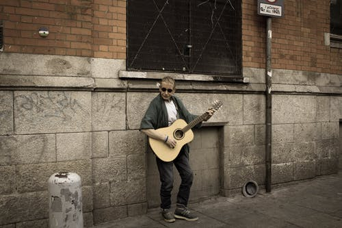 A Man Playing Acoustic Guitar on the Street