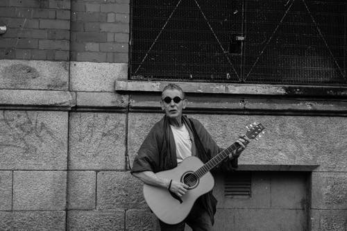 Grayscale Photo of a Man Playing Acoustic Guitar on the Street