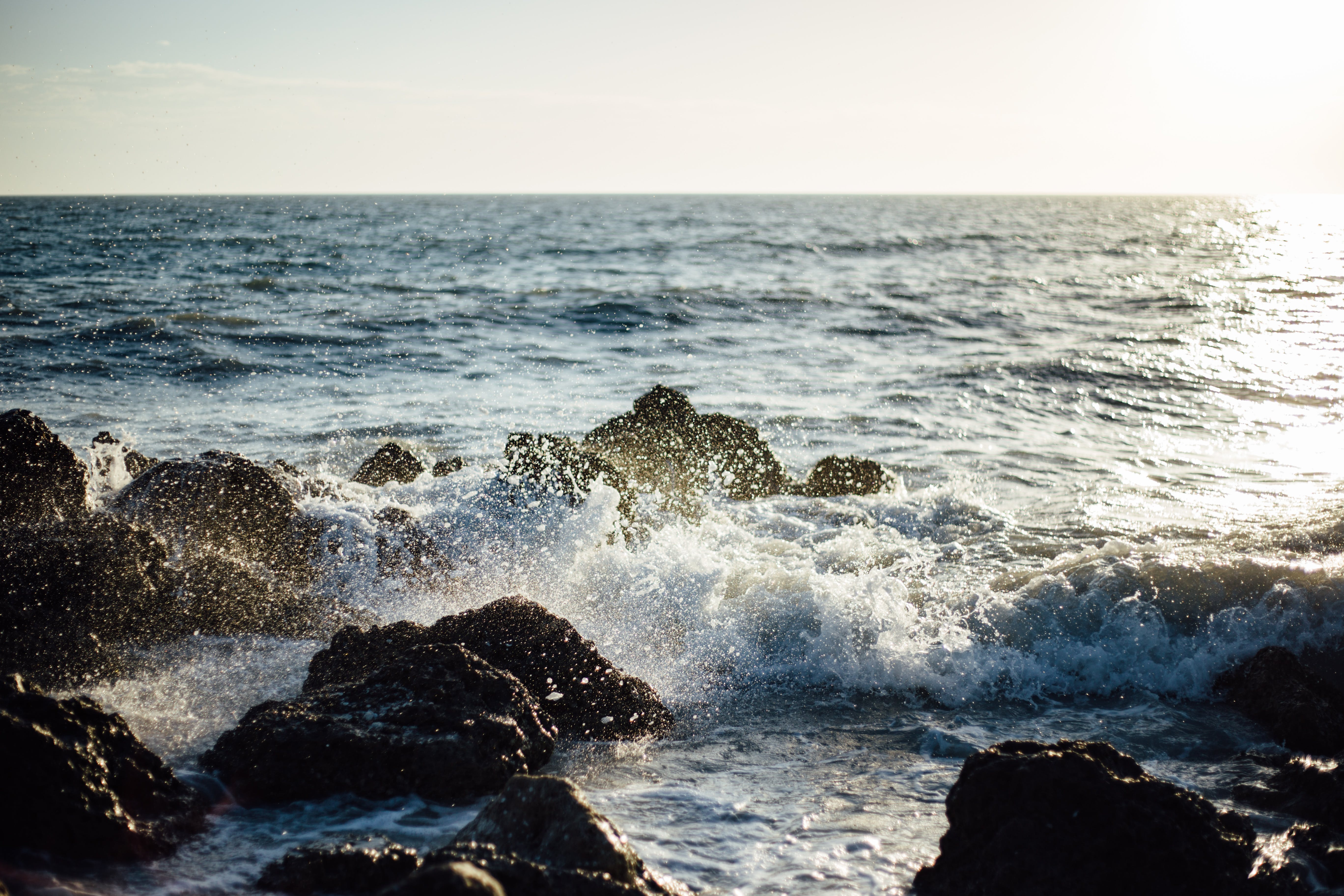 Photo of Blue Ocean Wave Coming to the Rocky Shore