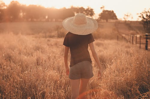 Back view of anonymous female in straw hat and casual wear walking on grassy field on countryside