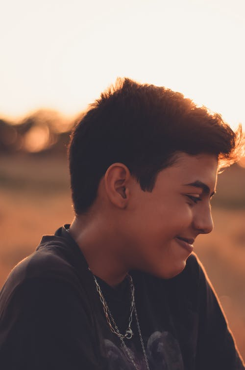 Modest smiling boy looking away