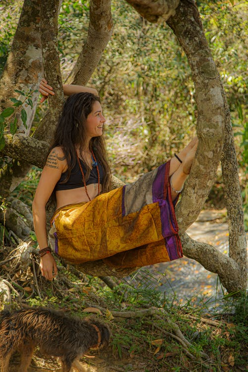 Full body side view of barefoot tattooed female in ornamental pants sitting on tree trunk in tropical forest with green plants
