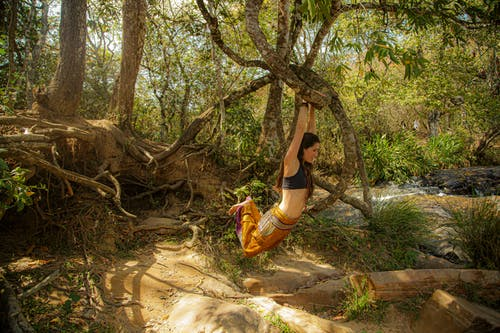 Active woman hanging on tree in forest