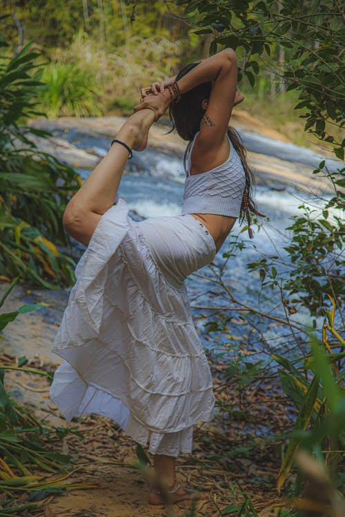 Full body side view of unrecognizable barefoot female standing on one leg while practicing yoga in woodland near flowing stream