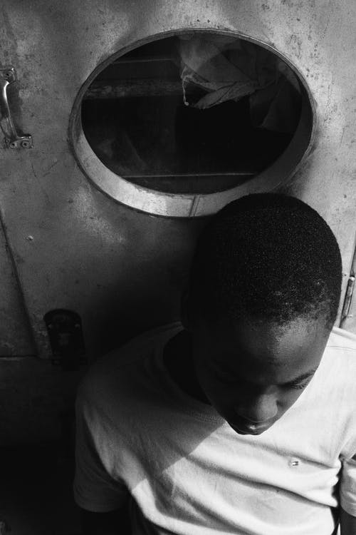 Black and white of focused African American male in casual clothes sitting on floor and leaning on metal door