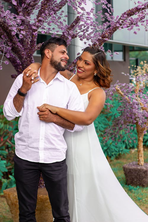 Positive ethnic couple in wedding outfits embracing and looking at each other while standing near blooming tree on street in city during holiday celebration