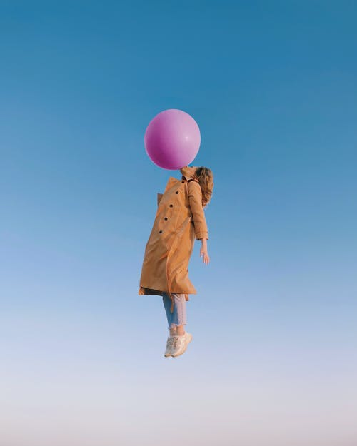 Side view of woman wearing trendy clothes with trench coat flying in sky and blowing enormous balloon