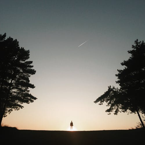 Small silhouette of unrecognizable person looking up on falling star in twilight sky
