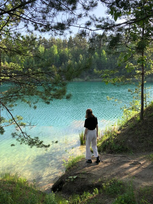Unrecognizable woman walking near lake in forest