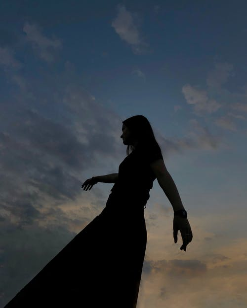 From below side view of woman with long hair spreading hands while enjoying evening time