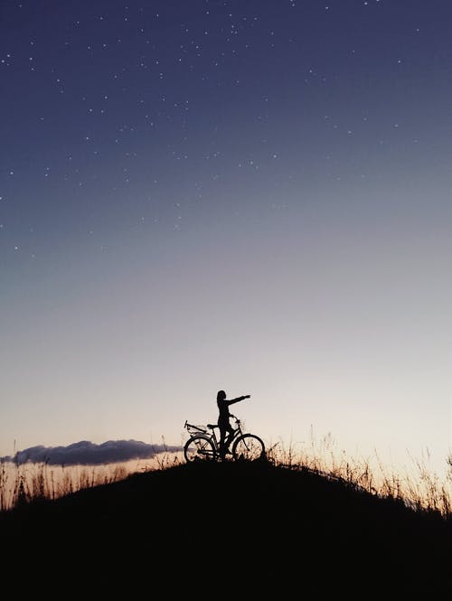 Side view of anonymous person on hill riding bicycle and stretching out hand in evening