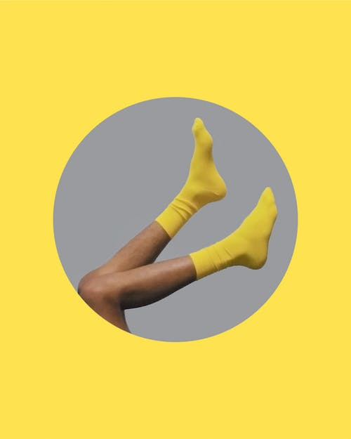 Side view of crop unrecognizable person in yellow socks in circle on gray background