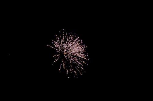 Glowing firework in dark sky