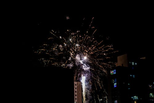 Bright firework bursting on dark sky over glowing residential houses on street in city during holiday celebration at night time