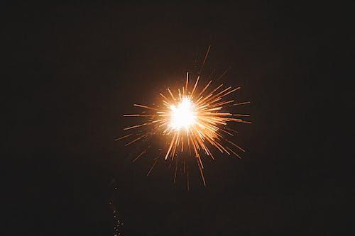 Bright firework illuminating dark sky