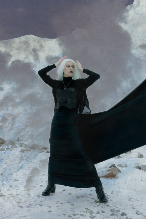 Mysterious lady in black costume standing on snowy terrain in winter