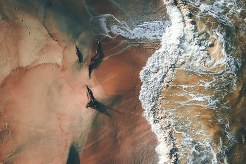 Drone view of broken trees placed on orange sandy shore washed with foamy wavy sea water